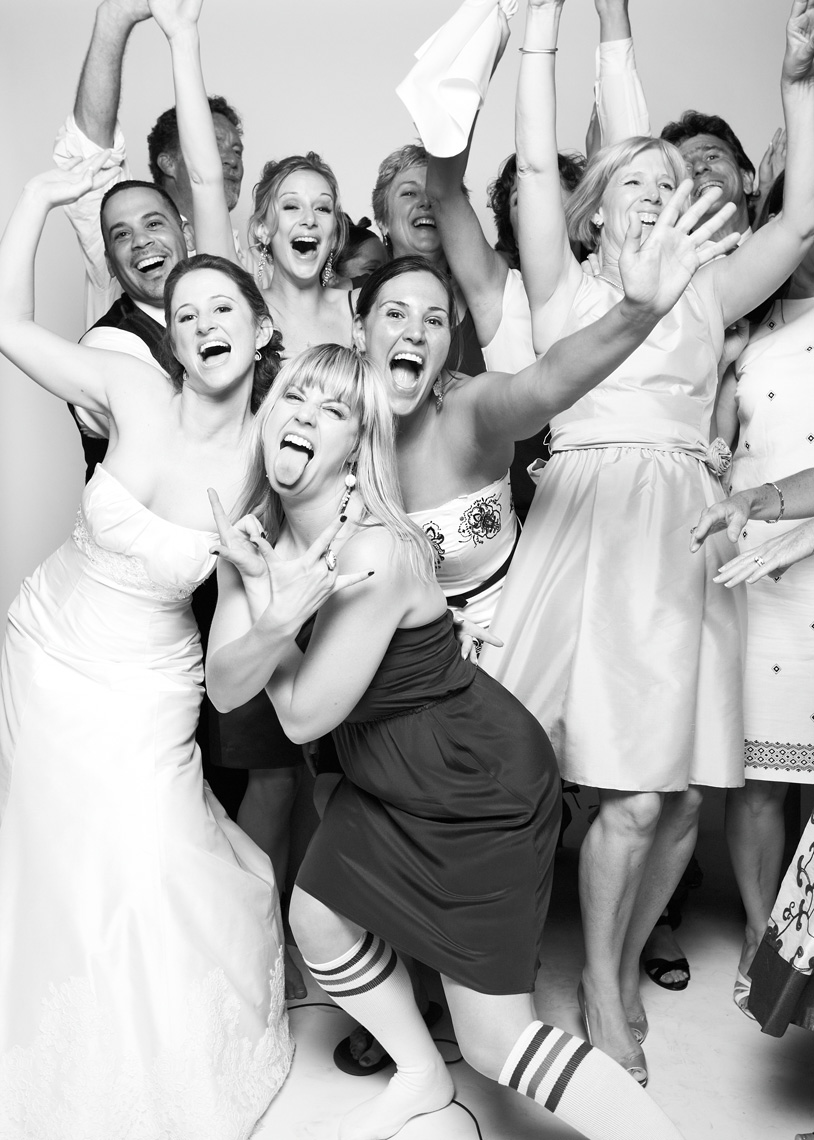 Bride poses with wedding guests in photo booth in San Francisco California