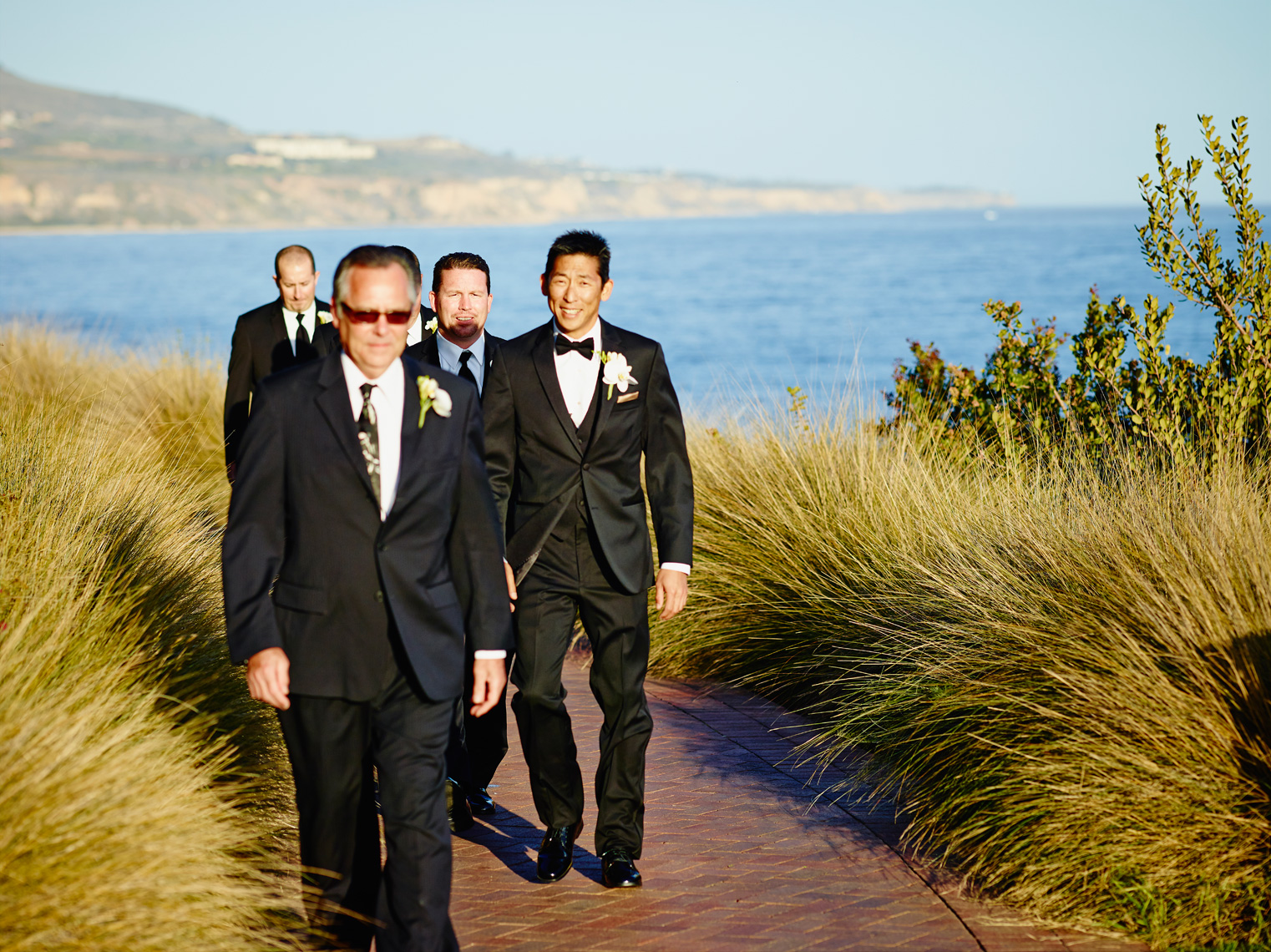 Groom and groomsmen walk into ceremony at Terranea Resort in Los Angeles, California