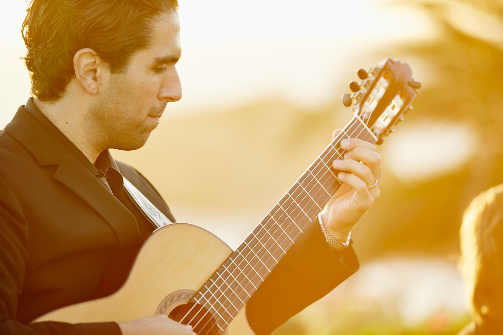 Musician plays guitar at sunset on Studio lawn at Montage Resort, Laguna Beach