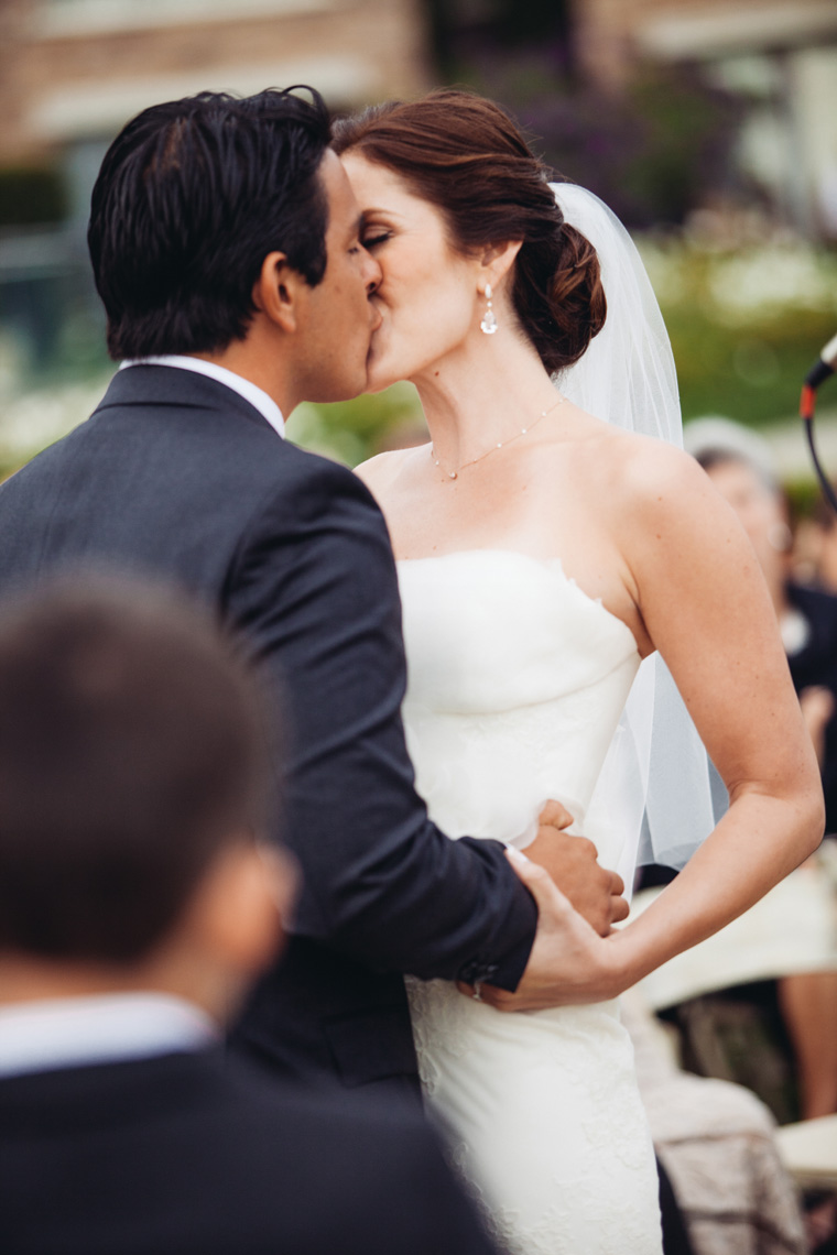 Bride and groom kiss during wedding ceremony on the Pacific Lawn at Montage Resort, Laguna Beach.