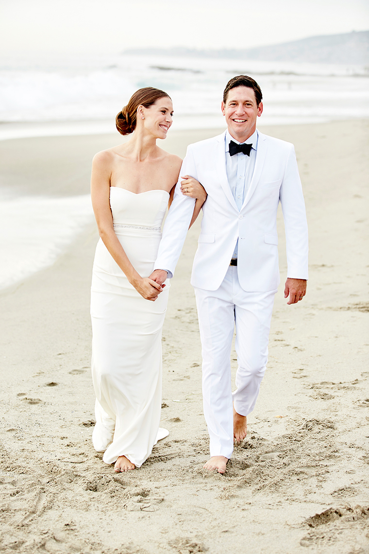 Bride and groom walk on Beach after ceremony ion Laguna Beach,  California
